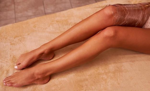 Primer plano de las piernas de una mujer joven durante una envoltura en una sesión de masaje en un salón de spa