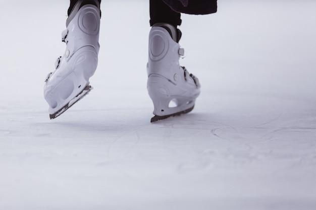 Primer plano de las piernas de las mujeres en patines en invierno en una pista de patinaje abierta, lugar para el texto