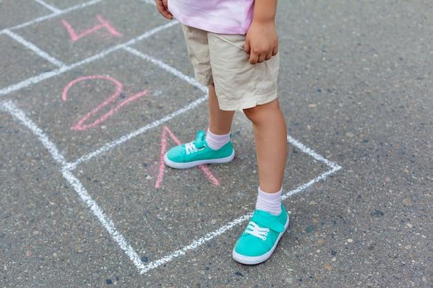 Primer plano de las piernas del niño y los clásicos pintados sobre asfalto. niña jugando al juego de rayuela en el patio de recreo afuera en un día soleado.