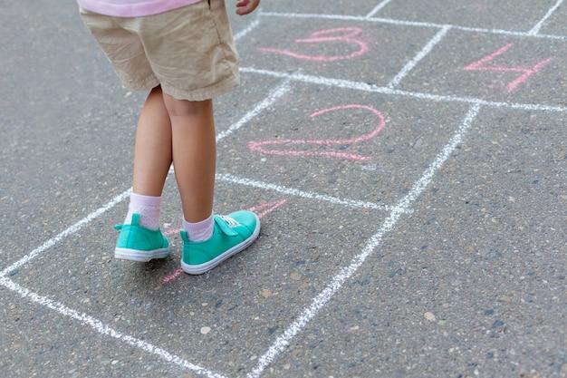 Primer plano de las piernas del niño y los clásicos pintados sobre asfalto.