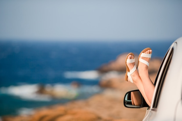 Primer plano de pies femeninos mostrando desde el mar de fondo de ventana de coche