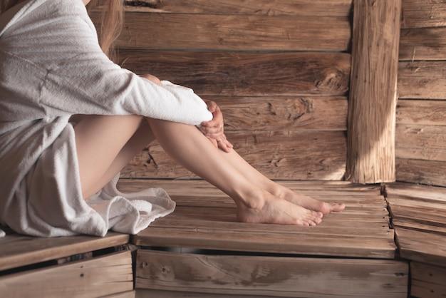 Primer plano de los pies de la mujer en el banco de madera en la sauna