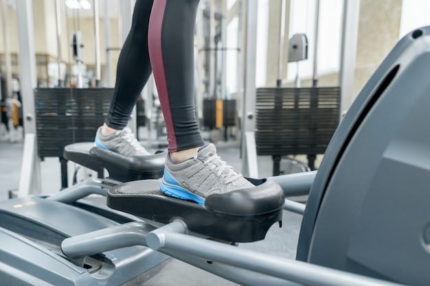 Primer plano de pies de mujer corriendo en la caminadora en el gimnasio