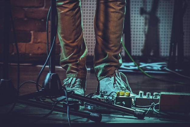 Primer plano de los pies de una persona cerca de los pedales de guitarra y un soporte de micrófono bajo las luces