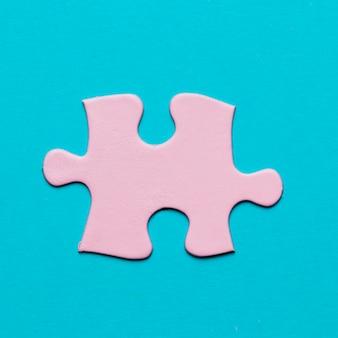 Primer plano de pieza de rompecabezas de color rosa sobre fondo azul