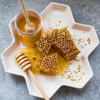 Primer plano de piezas de panal con tarro de miel en bandeja