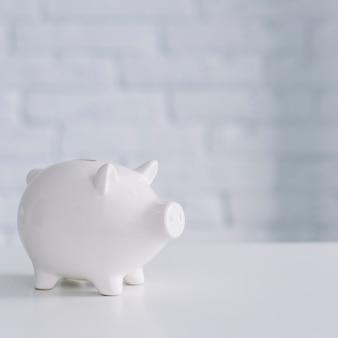 Primer plano de un piggybank blanco en el escritorio