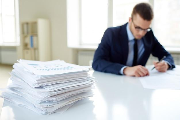 Primer plano de pila de documentos con ejecutivo de fondo