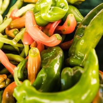 Primer plano de pimientos verdes y rojos en el puesto de mercado vegetal
