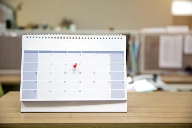 Primer plano de un pin en el calendario de escritorio en blanco.