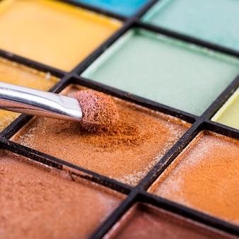 Primer plano de pincel de maquillaje con paleta de sombras de ojos de colores