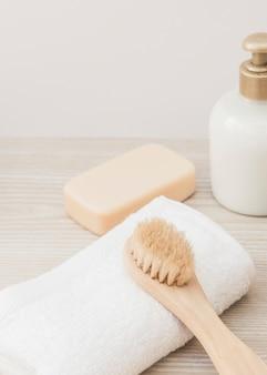 Primer plano de pincel; toalla; botella de jabón y cosmética en superficie de madera.