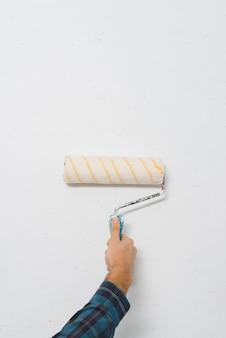 Primer plano de un pintor masculino pintando una pared con un rodillo de pintura con espacio de copia