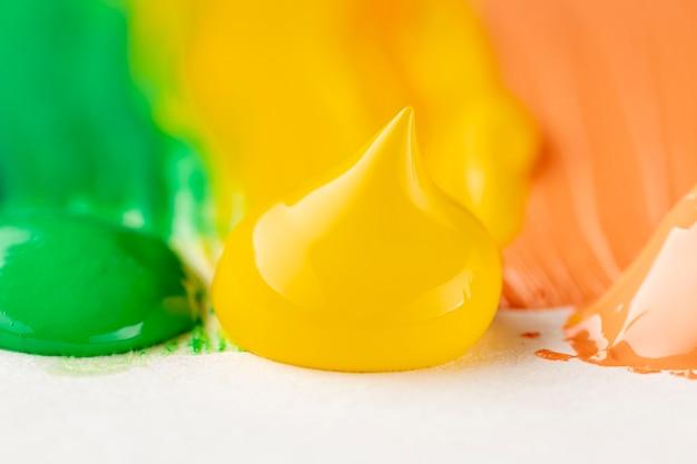 Primer plano de pintura amarilla, naranja y verde
