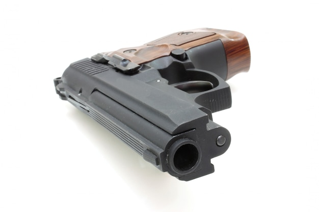 El primer plano de una pistola un blanco y cartuchos está aislado