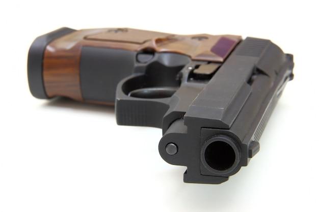 El primer plano de una pistola, un objetivo y cartuchos está aislado en un espacio en blanco