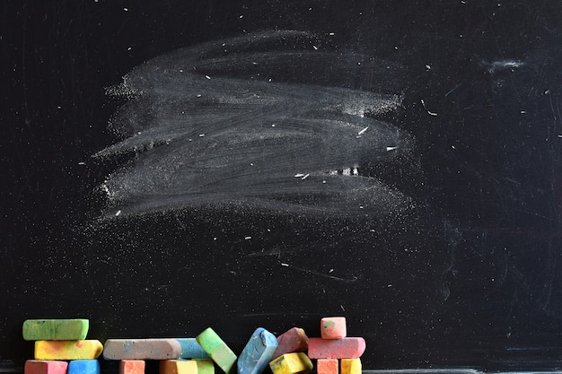 Primer plano de pizarra con trozos de tiza de colores