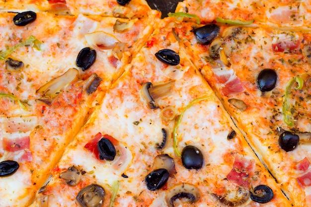 Primer plano de pizza con aceitunas tomate queso