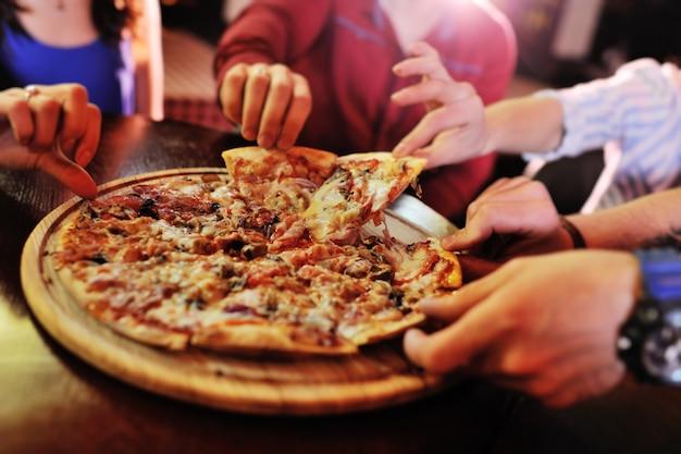 Primer plano de pizza caliente en una mesa en el fondo de un grupo o compañía de amigos de personas