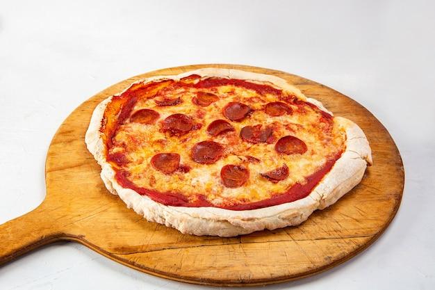 Primer plano de una pizza de pepperoni aislado sobre fondo blanco.