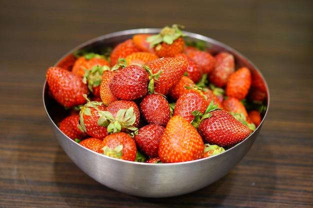 Primer plano de un plato de dulces fresas rojas sobre una mesa de madera