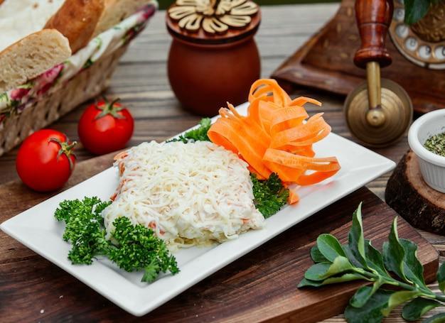 Un primer plano de plato de ensalada de mimosa con queso holandés en la parte superior