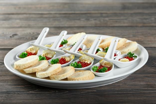 Primer plano de un plato grande, servido para un restaurante buffet con un sabroso aperitivo elaborado con caviar rojo, pan blanco, rodajas de limón y nata. se ve muy delicioso y bueno para banquetes y catering.