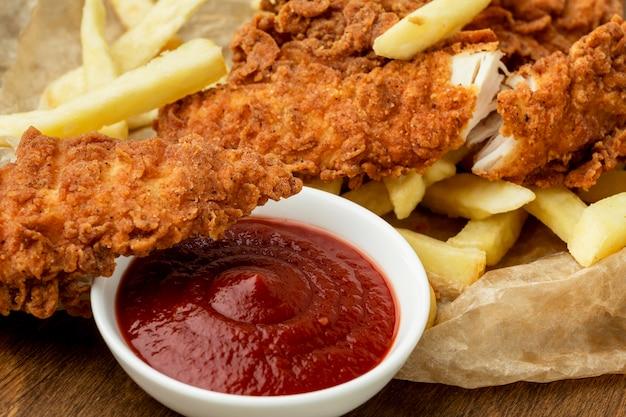 Primer plano de pollo frito y papas fritas con salsa de tomate