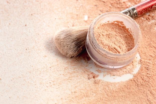 Primer plano de polvo mineral triturado brillo dorado color con pincel de maquillaje