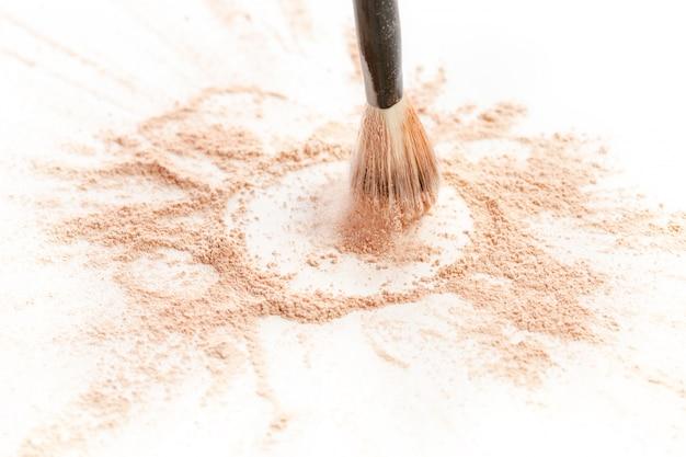 Primer plano de polvo mineral triturado brillo dorado con pincel de maquillaje