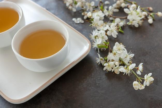 Primer plano de la porcelana de té asiático blanco conjunto con té verde japón con ramas en flor de cerezo