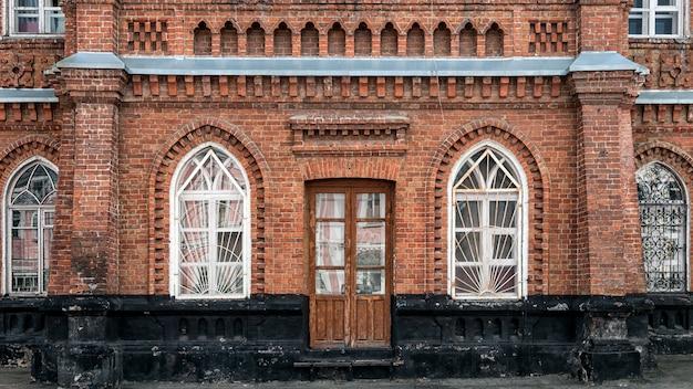 Primer plano de un porche de madera con una puerta marrón y ventanas antiguas con una casa antigua, una mansión de ladrillo antiguo