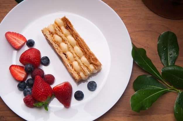 Primer plano de la porción de pastel y bayas frescas en un plato en la mesa