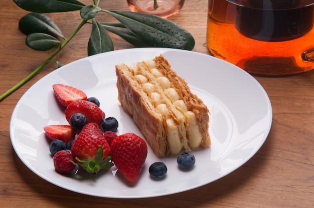 Primer plano de la porción de pastel de napoleón y bayas frescas en placa
