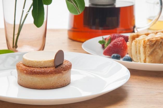 Primer plano de porciones de pasteles, bayas, vidrio y tetera en mesa