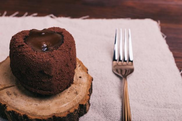 Primer plano de un postre de chocolate y un tenedor en una mesa