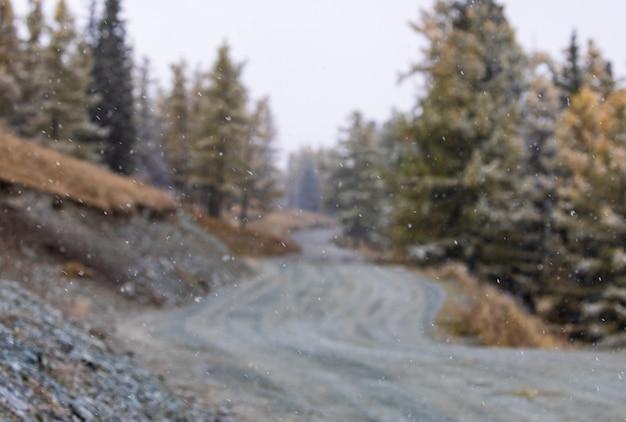 Primer plano de la primera nevada con un fondo borroso de una carretera de montaña rocosa. altai.