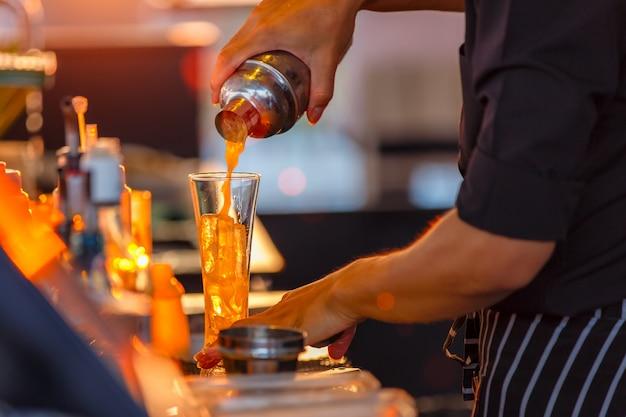 Primer plano del proceso de preparación de un cóctel de camareros de frutas de la pasión.