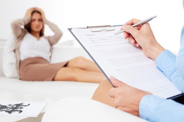 Primer plano de la psicóloga rellenando un informe