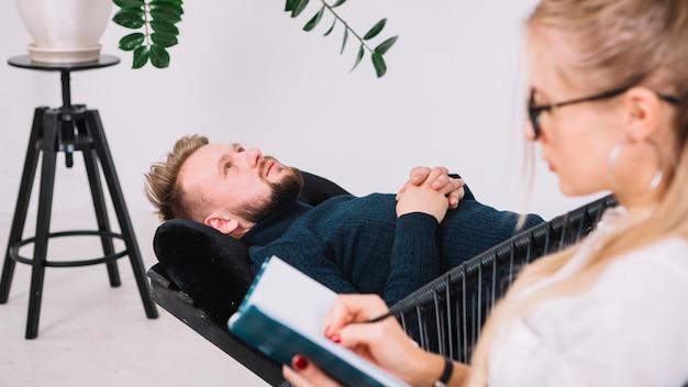 Primer plano del psicólogo femenino anotando notas durante la terapia con su paciente masculino