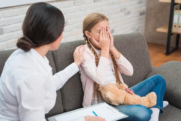 Primer plano de un psicólogo femenino dando apoyo a la niña llorando sentado en el sofá con oso de peluche