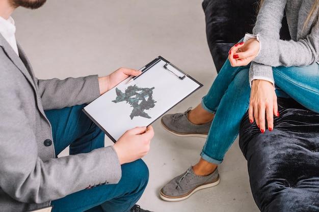 Primer plano de un psicólogo que muestra una mancha de tinta de rorschach en el portapapeles al paciente