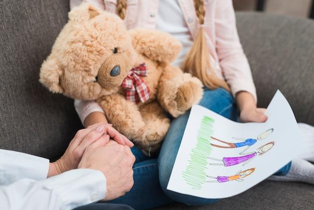 Primer plano de psicólogo sosteniendo la mano de una niña con papel de dibujo con familia dibujada