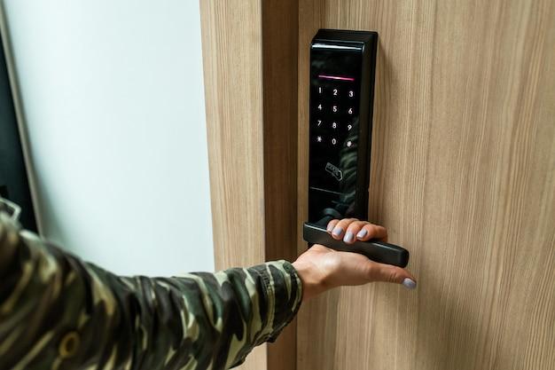 Primer plano: puerta abierta de mano de mujer en su habitación de hotel con cerradura inteligente