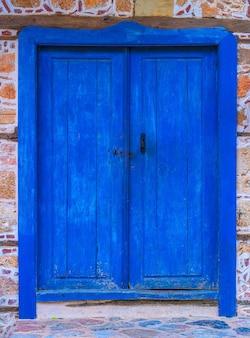 Primer plano de la puerta azul de madera vieja en un muro de piedra.