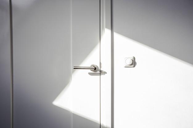 Primer plano puerta blanca con luz solar. puerta cromada, el interruptor de la luz en la pared diseño moderno vacío y limpio