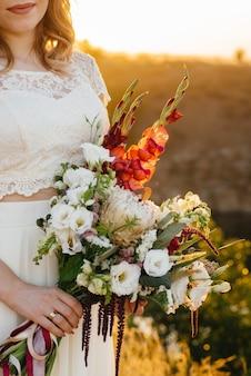 Primer plano de ramo de boda hermoso y sofisticado tiene a la novia en sus manos