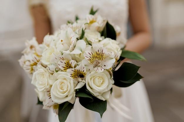 Primer plano de ramo de boda con rosas blancas y hojas verdes. la novia vestida tiene ramo.