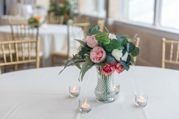Primer plano de un ramo de flores elegantes en un jarrón de cristal rodeado de velas sobre la mesa
