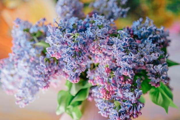 Primer plano de ramo de ramas de flores lilas en florero